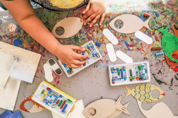 Child painting wooden fish