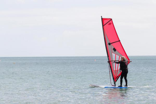 An elderly man keeping active and learning how to windsurf on a calm ocean in Coverack, Cornwall