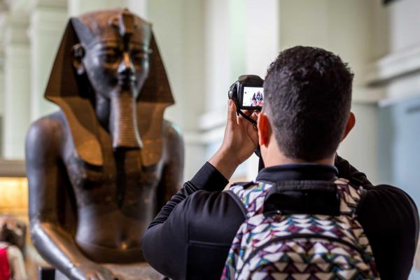 A male tourist taking photo of an Egyptian status brought from Egypt and kept in British Museum of London