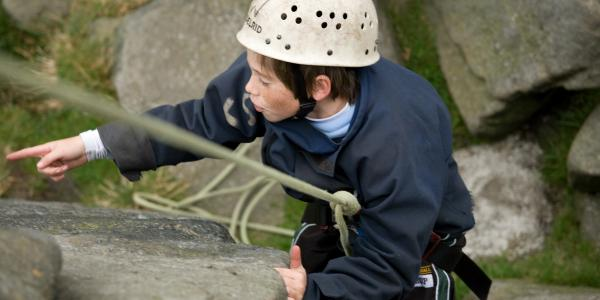 Boy abseiling down a rock face