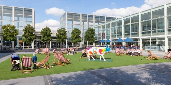 People sitting in deckchairs in the courtyard of Milton Keynes largest shopping centre, MK Centre.
