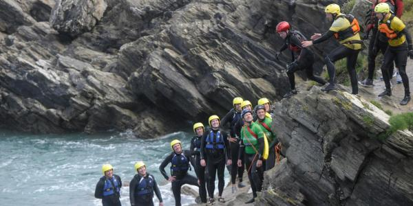 Group of people Coasteering on the Cliffs in Newquay, Cornwall