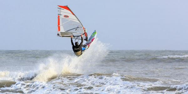 Windsurfer taking a jump, off Gower