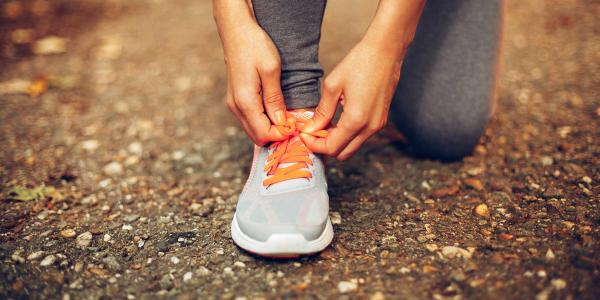 Runner tying shoe laces on trainer